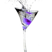 Crative image of a class with a purple olive splashing in it.