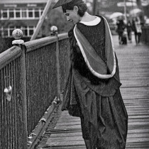 Lady in graduate clothes looking at love lock on a bridge