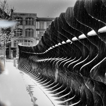 Shopper passing near a hudge iron fence in the snow