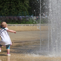 Little toddler trying to get in the fountain